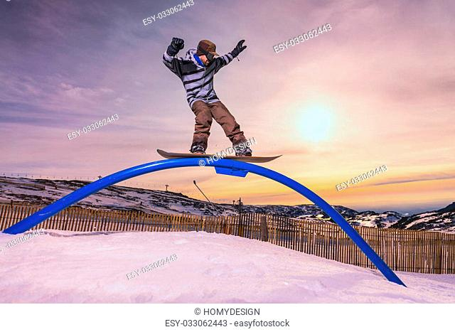A snowboarder executes a radical slide on a rail in a snow park