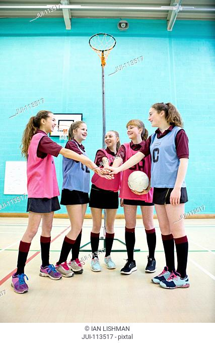 High school students touching hands in huddle before netball game in gym