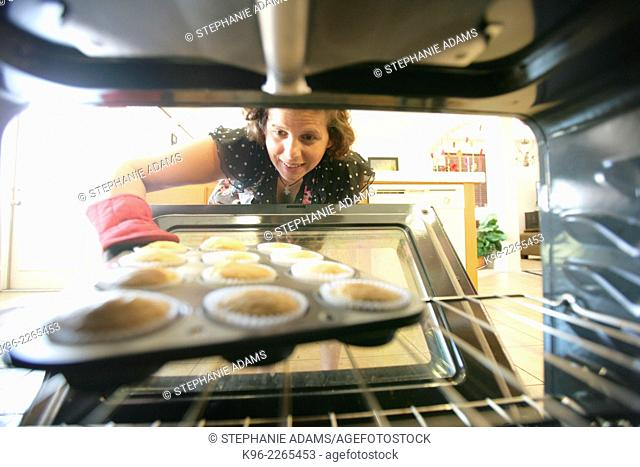 Looking out from inside the oven as a woman pulls out freshly baked cupcakes