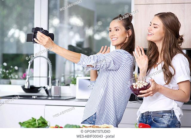 Food bloggers greeting their viewers in kitchen