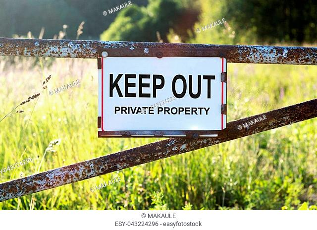 Sign Private Property and keep out on a metal gate on the dirt road