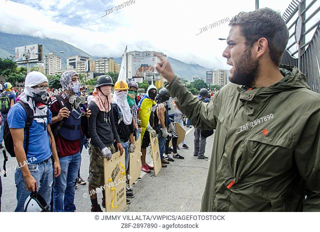 Deputy Juan Requesens speaks to the press in protest at the military base. Opposition protesters assembled on the Francisco Fajardo motorway