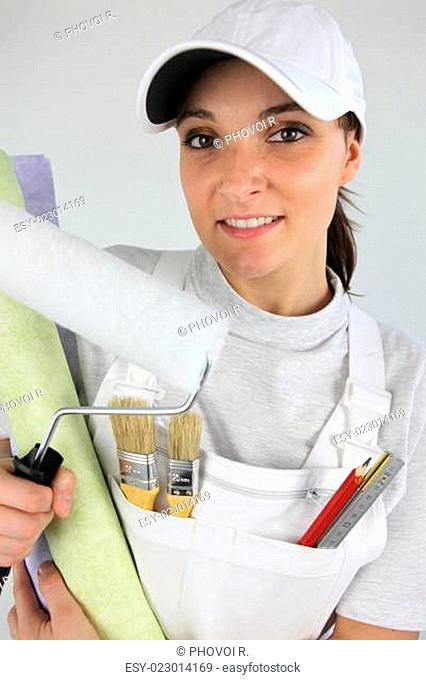 female painter with cap holding roller and wallpaper rolls