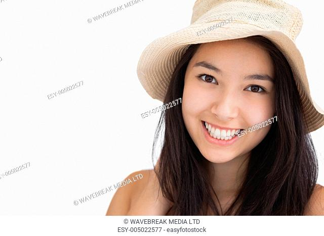 Smiling woman with a straw hat on white background