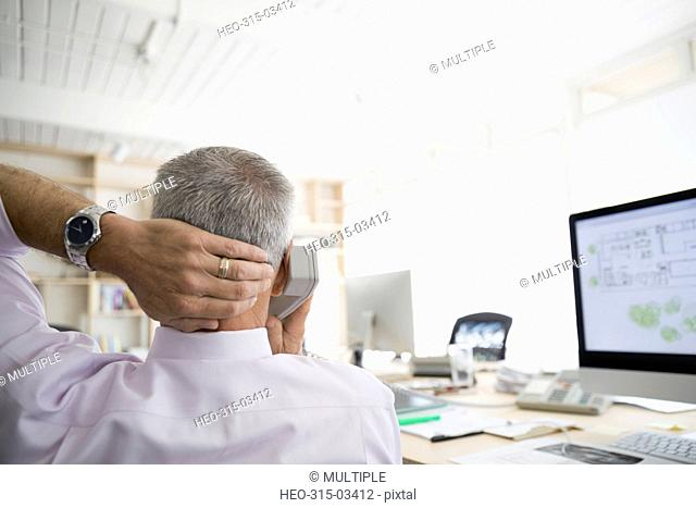 Male architect talking on telephone with hand behind head at computer in office