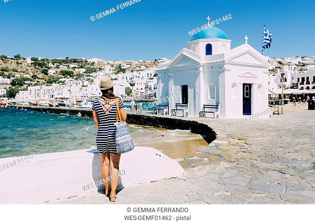 Greece, Mykonos, back view of tourist looking at the city