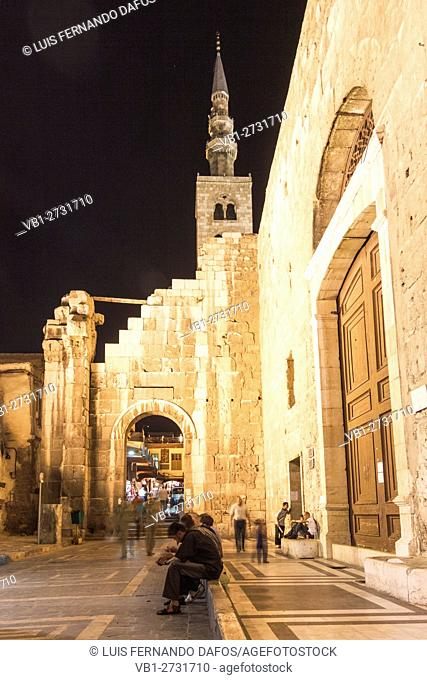 Men sitting at night at the rear door of the Umayyad Mosque in Damascus, Syria