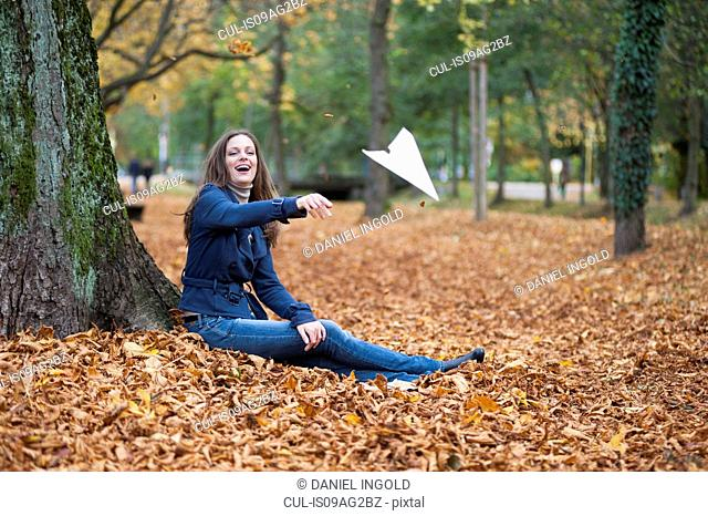 Young woman throwing paper plane in autumnal park