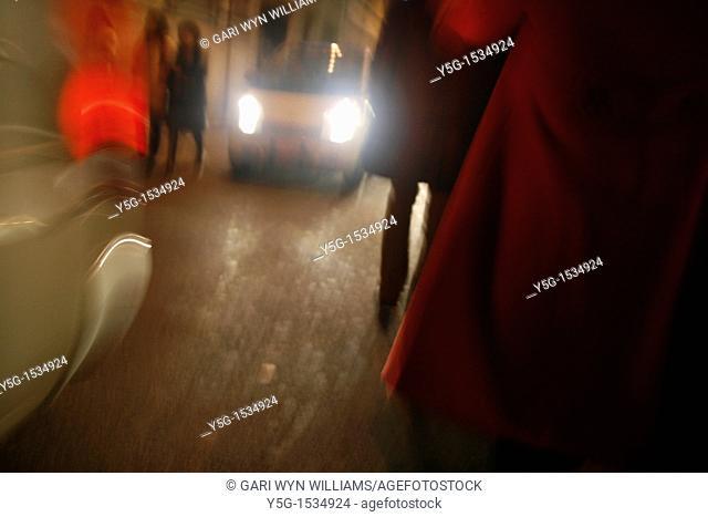 pedestrians walking in city street at night