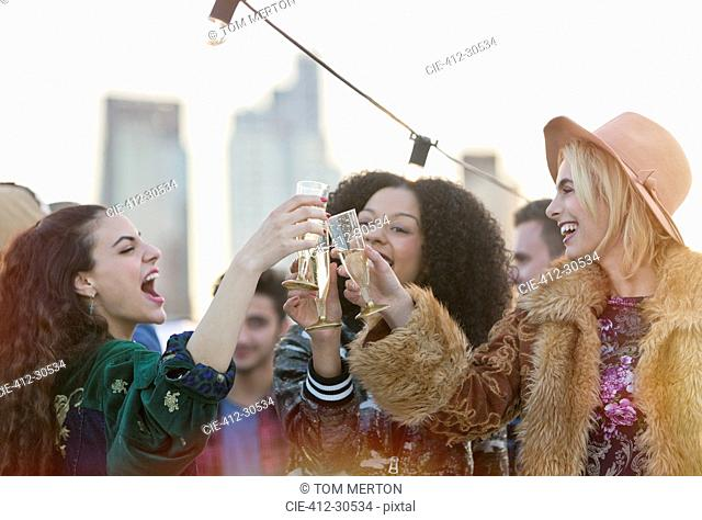Enthusiastic young women toasting champagne glasses at rooftop party