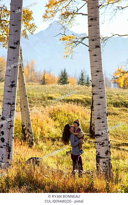 Mother holding toddler amongst silver birch trees