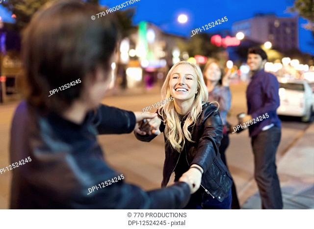 A young couple wearing black leather jackets being playful on a city sidewalk at night with friends watching in the background; Edmonton, Alberta, Canada
