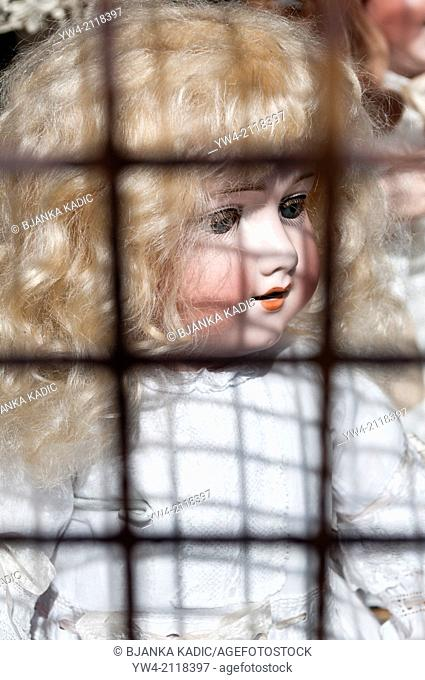 Doll behind shop grille