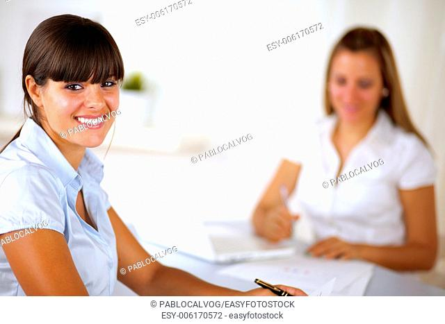 Hispanic young businesswoman looking at you at office while working on team