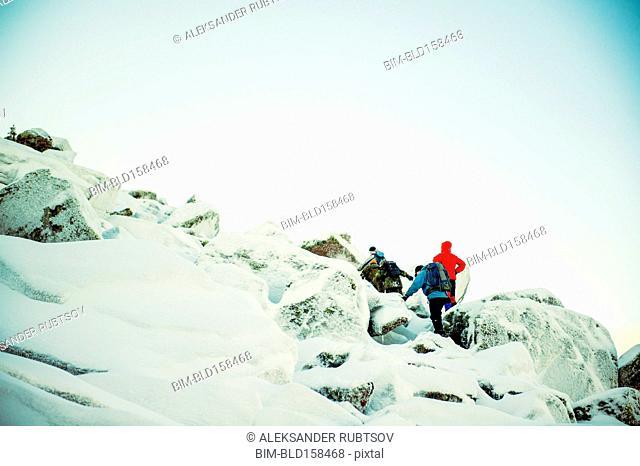 Caucasian hiker climbing snowy rock formations