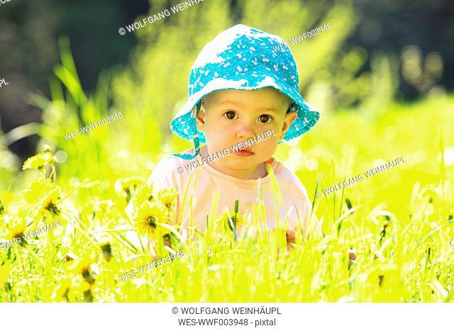 Portrait of baby girl wearing hat on flower meadow