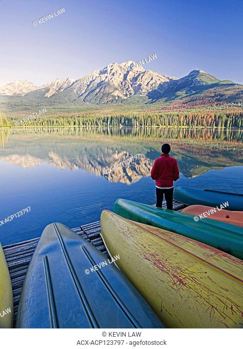 Lone middle age male standing on dock with canoes looking at Pyramid Mountain at Pyramid Lake, Jasper National Park, Alberta, Canada