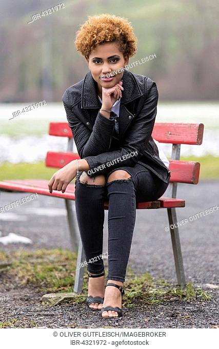 Young dark woman sitting on a bench, fashion