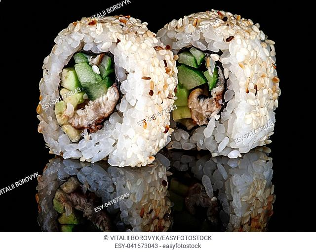Closeup two sushi roll california on black background. Sushi roll with eel, vegetables and unagi sauce. Reflection