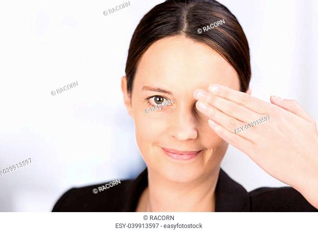 Attractive serious young woman covering one eye with her hand while looking at the camera with the other eye and smiling