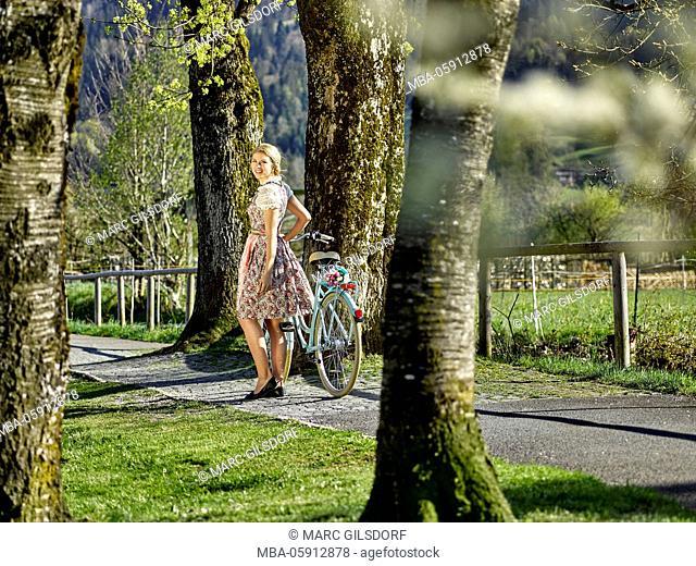 Woman by bicycle, dirndl