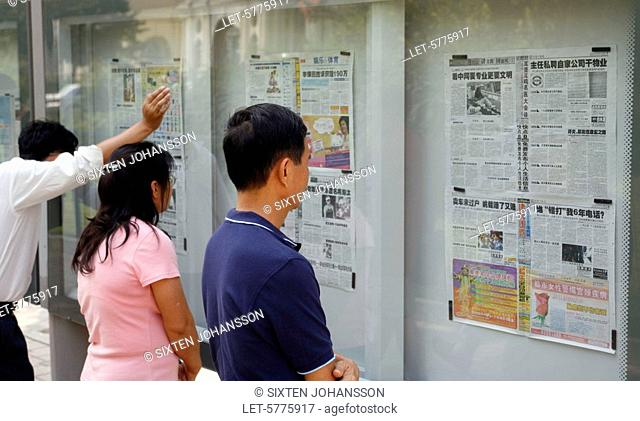 People reading wall newspapers in a glass cabinet on the street in Beijing. China