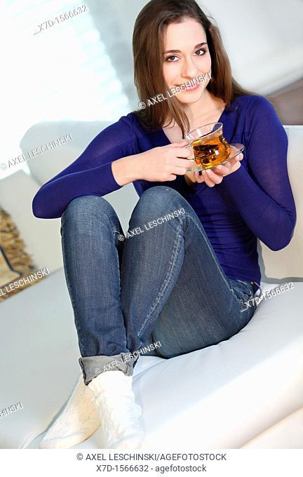 woman sitting on sofa drinking tea