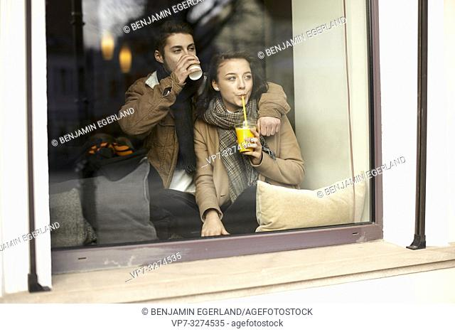 young teenage couple drinking takeaway orange juice and take-away coffee behind window in café, plastic cup and drinking straw, in Cottbus, Brandenburg, Germany