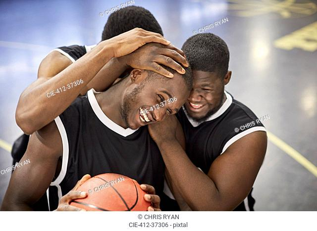 Happy young male basketball players hugging and celebrating after victory