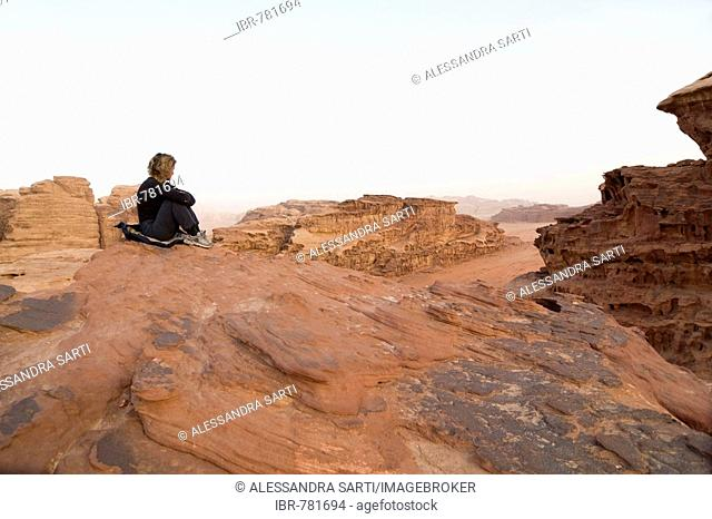 Woman sitting on a rock ledge looking off into the distance, Wadi Rum, Jordan, Middle East