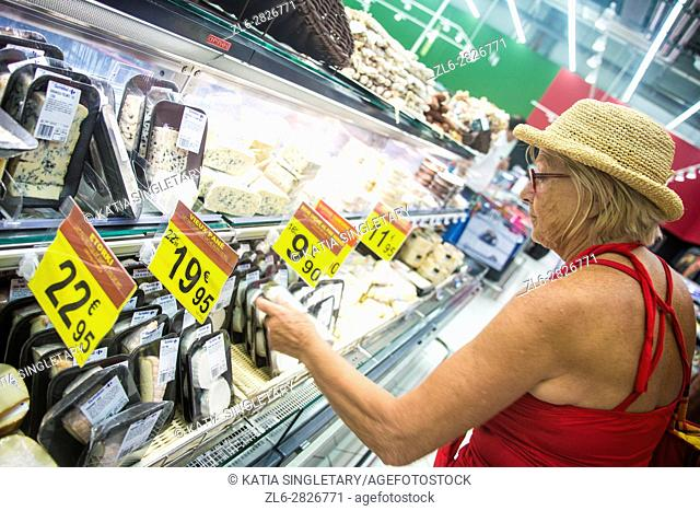 Caucasian woman pushing the grocery cart and buying cheese in the grocery store. She is choosing her food carefully and looking at prices!