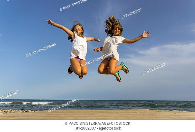 Girls playing, jumping on the beach, Alcocebre, Spain