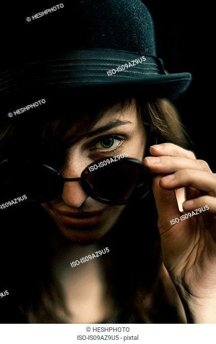 Portrait of woman looking over sunglasses at camera