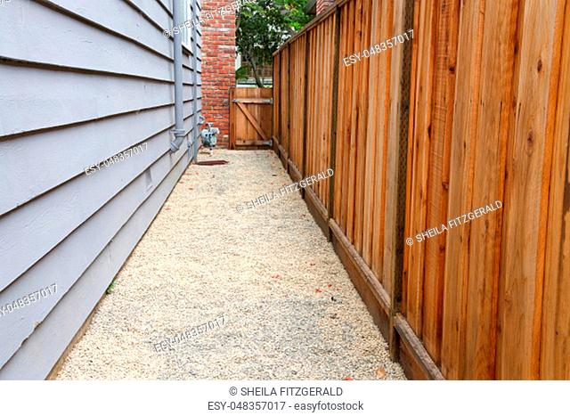 Long narrow side yard, new wood fence on the right with house on the left, home paint chipping and peeling. Meter by brick chimney exterior