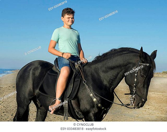 young boy and black stallion on the beach