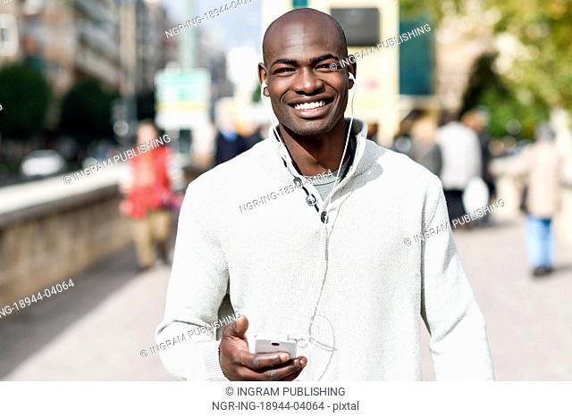 Black young man with a smartphone in his hand in urban background. Young african guy with shaved head wearing casual clothes and white headphones