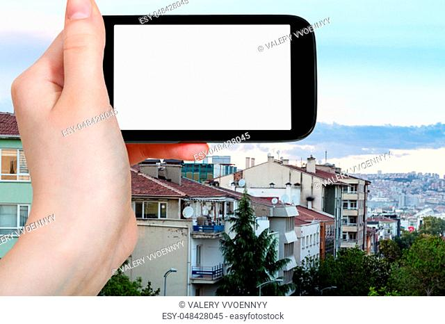 travel concept - tourist photographs of Kizilay residential district in Ankara city in spring evening in Turkey on smartphone with empty cutout screen with...