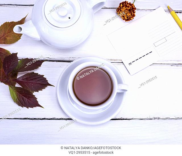 black tea in white round cup and saucer and empty postcard with yellow pencil, top view