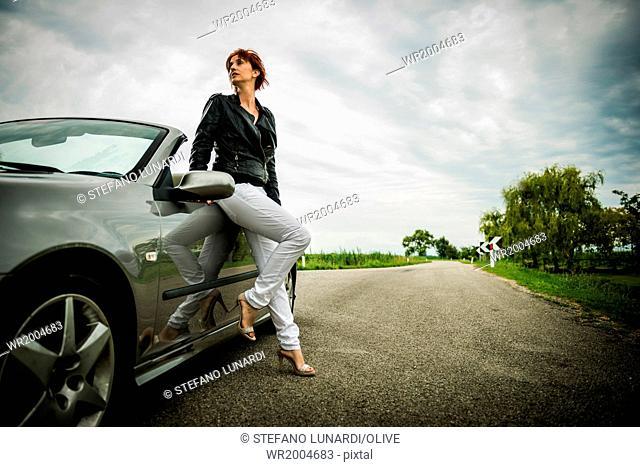 Woman posing next to her convertible car