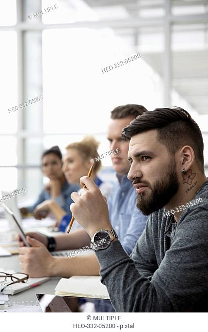 Serious, attentive businessman with digital tablet listening in meeting