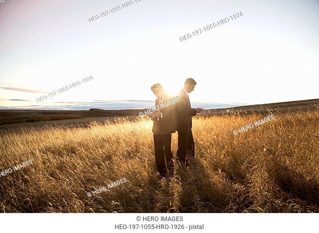 Businessmen using digital tablets on field
