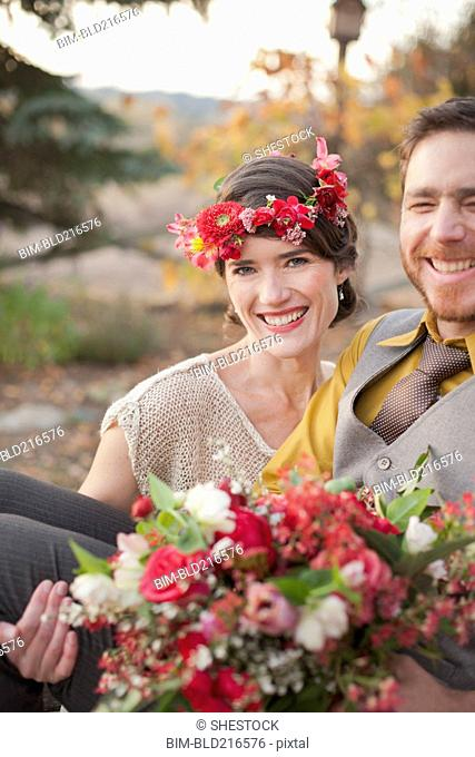 Bride carrying groom and bouquet in rural field