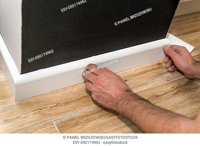 Close up of mans hands fitting skirting board