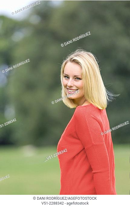 Portrait of a pretty blonda woman in Park smiling at Camera