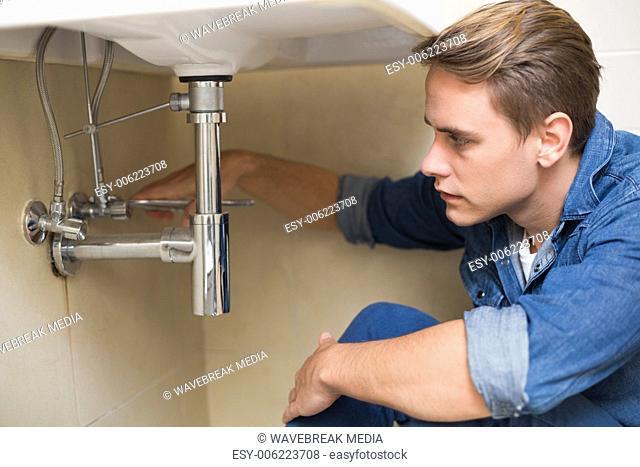 Handsome plumber repairing washbasin drain in bathroom
