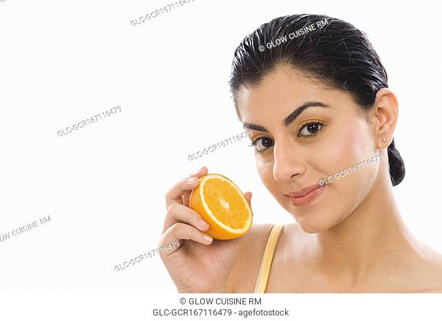 Portrait of a woman holding a half of orange