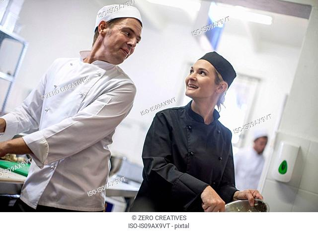 Chefs chatting and preparing food in kitchen