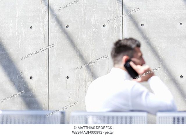 Businessman on cell phone in front of concrete wall