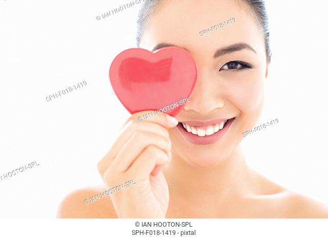 MODEL RELEASED. Young Asian woman covering eye with heart, portrait