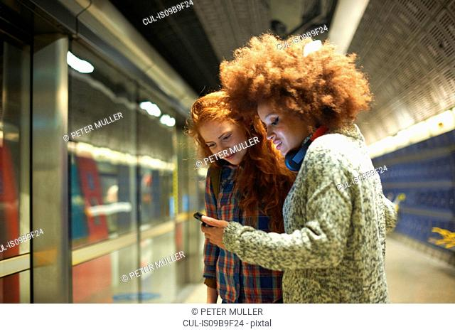 Two young women at train station, looking at smartphone